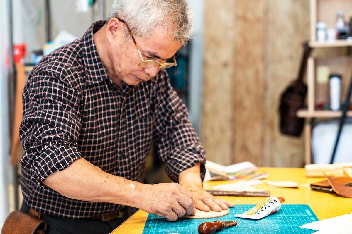 職人師傅No2.頑皮小孩皮革工坊_邱芳珍師傅 邱大哥生活在三峽幾十年了,以前是一位資深園丁,退休後自學皮革創作玩出興趣,決定成為工坊的師傅,享受著實踐自己的創作興趣,也將這樣的興趣透過體驗的方式跟更多居民和旅客交流。 | 合習聚落 | 三峽工藝&產業的共好實踐基地