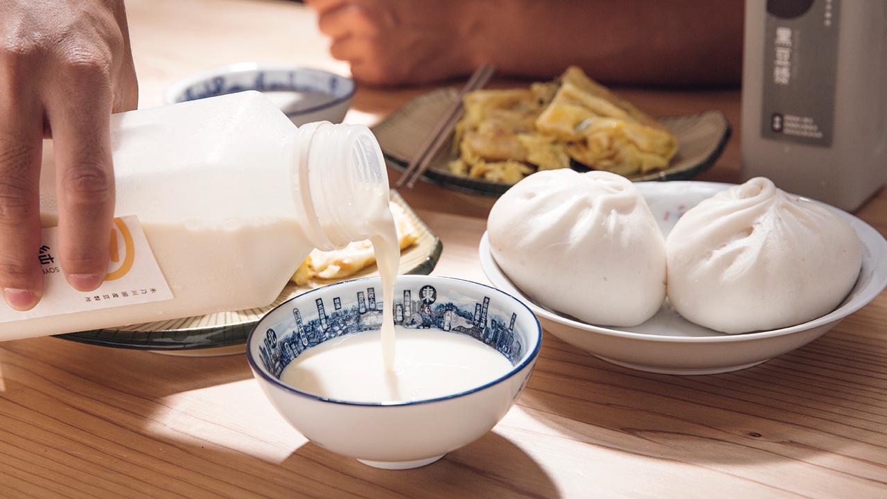 從外觀上無法直接判別的非基改黃豆與基改黃豆,兩者在價格上相差了二至三倍,導致台灣食品中到處充斥著基改黃豆的影子,但在國外早已有研究指出食用基改黃豆有增加不孕、器官病變和罹癌機率的可能性,並且在提高了產量的背後,基改黃豆殖入了抗除草劑及抗蟲基因,雖然因此減少殺蟲劑使用量,卻更肆無忌憚噴灑除草劑,農藥的使用反而比以往更多,在基改黃豆無所不在的現今,我們也許在不知不覺間已經將可能有致癌風險的除草劑嘉磷塞喝下肚了,相比於非基改豆漿,飲用基改豆漿看似比較便宜,實際上可能增加了不少健康疑慮與食安風險。 | 改變生命的豆漿店